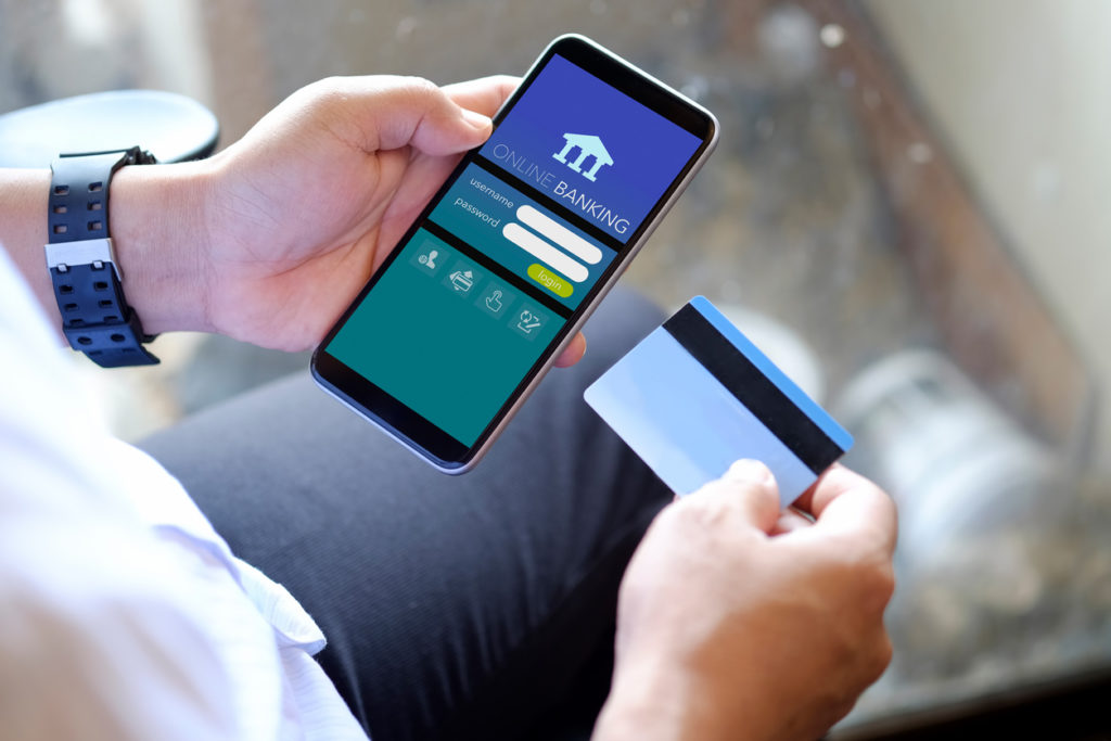 Cropped shot of man using online banking app on mobile phone for online payment via credit card.